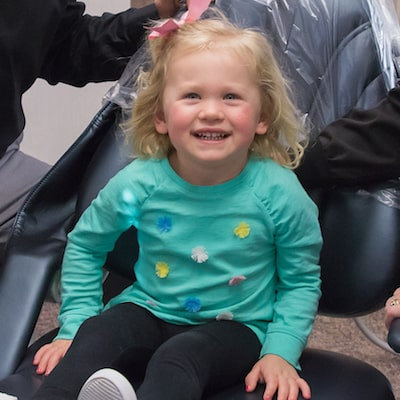 Little girl sitting in the dentist chair and smiling
