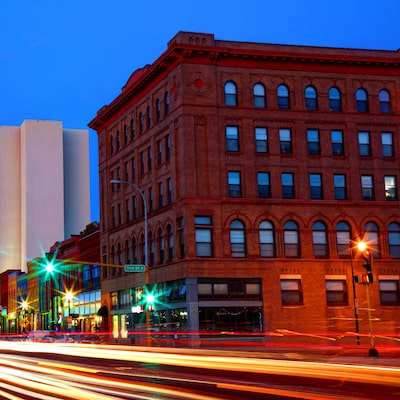 Building in Fargo at night with car lights speeding by to show that Fargo is a large, fast moving city with a small town feel.