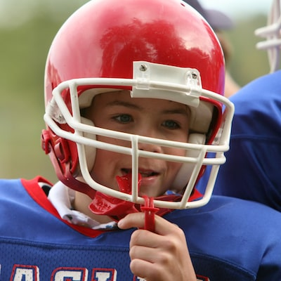 Boy wearing a red football helmet with a mouthguard hanging from his mouth
