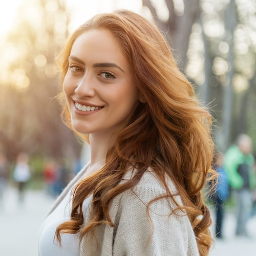Woman with red hair in an autumn outfit and smiling outside