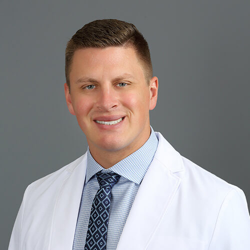 Dr. Vetter, our dentist in Fargo, ND smiling and wearing a white dental coat